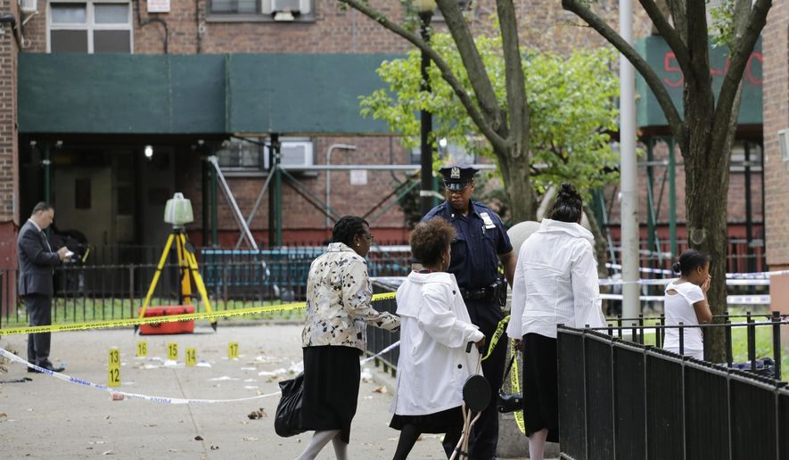 A girl, right, holds her hands to her mouth as she passes the scene of a triple homicide, left, Sunday, Sept. 20, 2015 at the Ingersoll Houses in the Brooklyn borough of New York. Three men were killed at the scene at 2 a.m. Sunday, according to police. (AP Photo/Mark Lennihan)