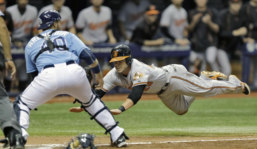 Baltimore Orioles' Steve Pearce dives towards home plate before the throw to Tampa Bay Rays catcher J.P. Arencibia (40) during the eighth inning of a baseball game Sunday, Sept. 20, 2015, in St. Petersburg, Fla.  Pearce scored on third baseman Evan Longoria's error on a ground ball by Paul Janish. (AP Photo/Chris O'Meara)