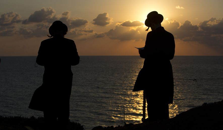 """Ultra-Orthodox Jews of the Hassidic sect Vizhnitz gather on a hill overlooking the Mediterranean sea as they participate in a Tashlich ceremony in Herzeliya, Israel, Thursday, Oct. 2, 2014. Tashlich, which means """"to cast away"""" in Hebrew, is the practice by which Jews go to a large flowing body of water and symbolically """"throw away"""" their sins by throwing a piece of bread, or similar food, into the water before the Jewish holiday of Yom Kippur, which start on Friday. (AP Photo/Oded Balilty)"""