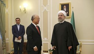 Iranian President Hassan Rouhani, right, welcomes U.N. nuclear chief Yukiya Amano for their meeting in Tehran, Iran, Sunday, Sept. 20, 2015. Rouhani told Amano on Sunday that his agency should be fair in its implementation of a nuclear deal reached between Iran and the world powers, according to a report on Rouhani's website. (AP Photo/Vahid Salemi)