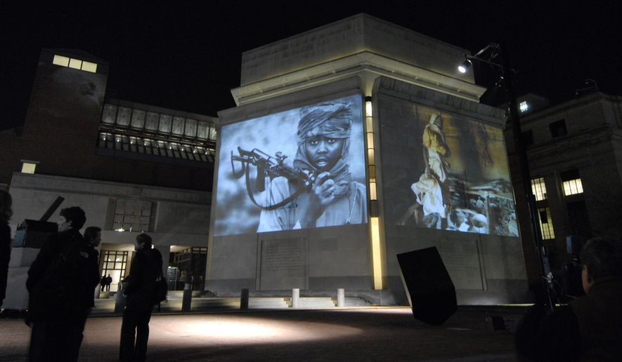 In this Monday, Nov. 20, 2006, file photo, images from Darfur and Chad are projected on the exterior walls of the United States Holocaust Memorial Museum in Washington. To try to predict and prevent mass killings, the museum is making both sophisticated statistical analysis and feedback from experts publicly available for the first time to produce early warnings that can help governments, policy makers, advocacy groups and scholars decide where to concentrate their efforts. The Early Warning Project online tool was announced Monday, Sept. 21, 2015. (AP Photo/Nick Wass)