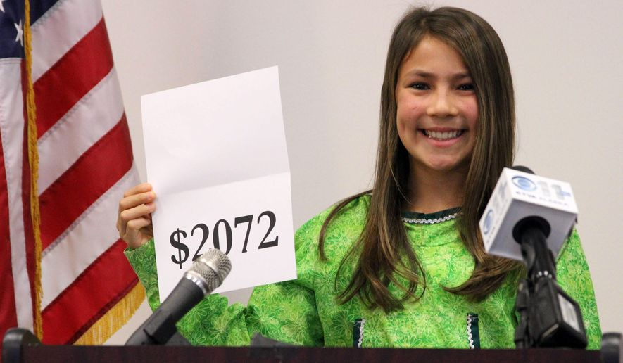 Seventh-grade student Shania Sommer of Palmer, Alaska, announces that nearly every Alaskan will receive $2,072 from this year's oil dividend check during a news conference Monday, Sept. 21, 2015, in Anchorage, Alaska. Sommer was chosen by the office of Gov. Bill Walker to reveal the amount of this year's check. (AP Photo/Mark Thiessen)
