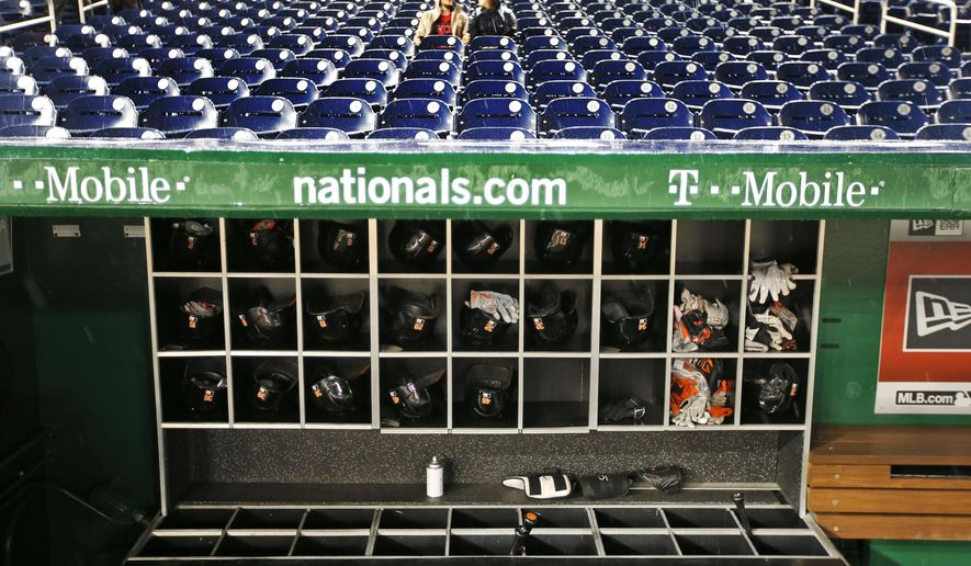 Fans sit in stands as rain falls before a baseball game between the Washington Nationals and the Baltimore Orioles at Nationals Park, Monday, Sept. 21, 2015, in Washington. The game was postponed and is to be played Thursday, Sept. 24. (AP Photo/Alex Brandon)