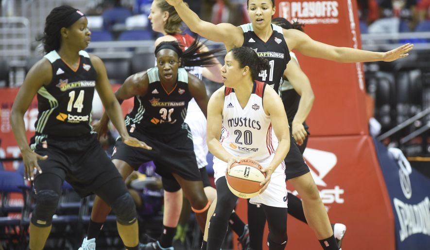 Washington Mystics' Kara Lawson (20) is surrounded by  New York Liberty's Sugar Rodgers (14), Tina Charles (31) and Kiah Stokes (41) during the second half of a WNBA basketball playoff game on Sunday, Sept. 20, 2015, in Washington. (AP Photo/Kevin Wolf)