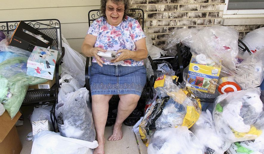 In this Sept. 2, 2015 photo, Betty Reckwerdt flattens and folds plastic bags on her porch at home in Island Lake, Ill. Reckwerdt is one of dozens of women who participate in Mats for the Homeless, a loose collection of McHenry and Lake county residents who have been transforming plastic bags into mats for the homeless since 2012. (Matthew Apgar/Northwest Herald via AP)  CHICAGO TRIBUNE OUT, MANDATORY CREDIT