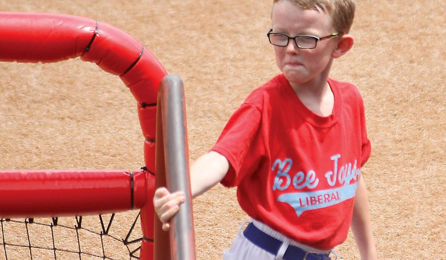 FILE - In this Aug. 1, 2015, file photo, bat boy Kaiser Carlile, 9, gets ready for a National Baseball Congress World Series baseball game between the Liberal Bee Jays and San Diego Waves outside the dugout in Wichita, Kan. The sale of a 1962 autographed World Series baseball has raised $30,000 for a memorial statue honoring Carlile, the batboy who died when he was accidentally hit by a bat during a game. (Earl Watt/Leader & Times via AP) MANDATORY CREDIT