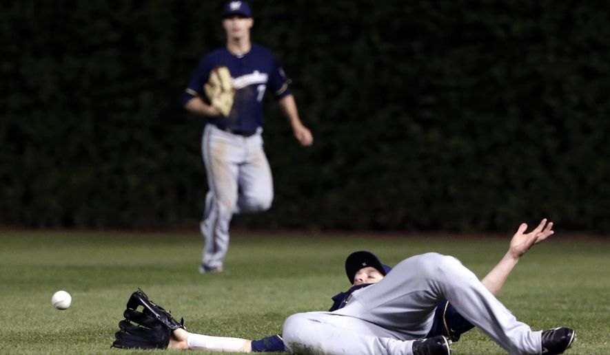 Milwaukee Brewers right fielder Shane Peterson is unable to catch a shallow fly ball from Chicago Cubs' Starlin Castro during the seventh inning of a baseball game Monday, Sept. 21, 2015, in Chicago. (AP Photo/Charles Rex Arbogast)