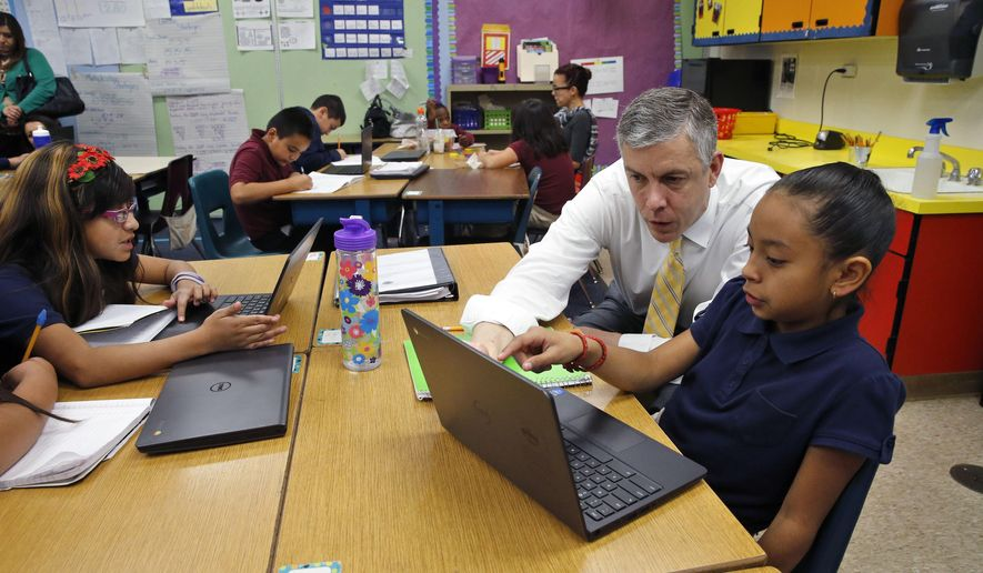 FILE - In this Tuesday, Feb. 24, 2015 file photo, U.S. Education Secretary Arne Duncan visits with 9-year-old Nadia Garcia in a third grade classroom at McGlone Elementary School in Denver. The Colorado Supreme Court has rebuffed a challenge to how the state funds public schools on Monday, Sept. 21, 2015, a decision that will change how lawmakers are allowed to tackle school budgets during a recession. (AP Photo/Brennan Linsley, file)