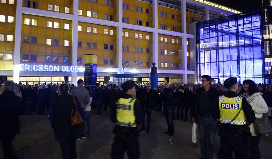 Police and concertgoers wait for the U2 concert outside the Ericsson Globe Arena in Stockholm, Sweden Sunday, Sept. 20, 2015. U2 has canceled a concert in Sweden after a security breach prompted police to evacuate the Globe Arena in Stockholm. Police said they stopped the event late Sunday due to a security problem as spectators entered the arena. (Pontus Lundahl /TT News Agency via AP) SWEDEN OUT