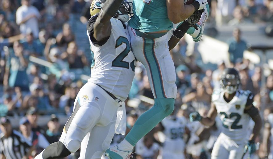 Miami Dolphins tight end Jordan Cameron (84) makes the catch against Jacksonville Jaguars James Sample (23)  during the first half of an NFL football game, Sunday, Sept. 20, 2015, in Jacksonville, Fla. (AP Photo/Phelan M. Ebenhack)