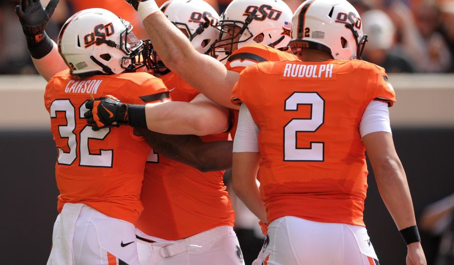 Oklahoma State running back Chris Carson, left, celebrates his first quarter touchdown with wide receiver David Glidden, left center, offensive lineman Brad Lundblade, right center, and quarterback Mason Rudolph, right, during an NCAA college football game in Stillwater, Okla., Saturday, Sept. 19, 2015. Carson had 104 yards rushing and 2 touchdowns in the 69-14 win over UTSA. (AP Photo/Brody Schmidt)