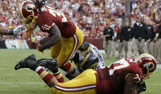 Washington Redskins running back Matt Jones (31) dives into the end zone over teammate guard Shawn Lauvao (77) for a touchdown after breaking a tackle from St. Louis Rams middle linebacker James Laurinaitis (55) during the second half of an NFL football game in Landover, Md., Sunday, Sept. 20, 2015. (AP Photo/Patrick Semansky)