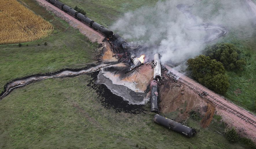 FILE - In this Sept. 19, 2015, file photo, smoke rises from a burning ethanol tanker car after the BNSF train derailed in a rural part of Bon Homme County awash in corn fields between the towns of Scotland and Lesterville, S.D. Federal investigators looking into a weekend train derailment in rural South Dakota on Monday, Sept. 21 began to interview the engineer and conductor of the train, seven of whose ethanol tanker cars left the tracks, causing at least one to catch on fire. (Dave Tunge/Dakota Aerials via AP, File)