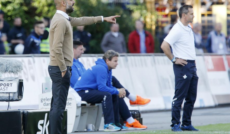 Bayern head coach Pep Guardiola, left, and Darmstadt's coach Dirk Schuster instruct their players during a German first division Bundesliga soccer match between Darmstadt 98 and Bayern Munich in Darmstadt, Germany, Saturday, Sept. 19, 2015.(AP Photo/Michael Probst)