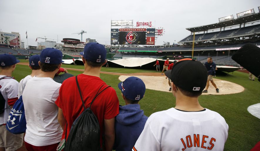 Fans watch members of the grounds crew cover the field as the rain falls before a baseball game between the Washington Nationals and the Baltimore Orioles at Nationals Park, Monday, Sept. 21, 2015, in Washington. (AP Photo/Alex Brandon)