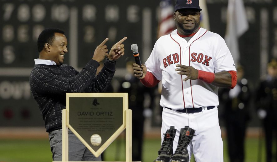 Former Boston Red Sox pitcher Pedro Martinez, left, smiles and points toward Red Sox's David Ortiz as Ortiz takes the microphone during ceremonies held to honor his 500 career home runs before a baseball game against the Tampa Bay Rays, Monday, Sept. 21, 2015, at Fenway Park, in Boston. (AP Photo/Steven Senne)