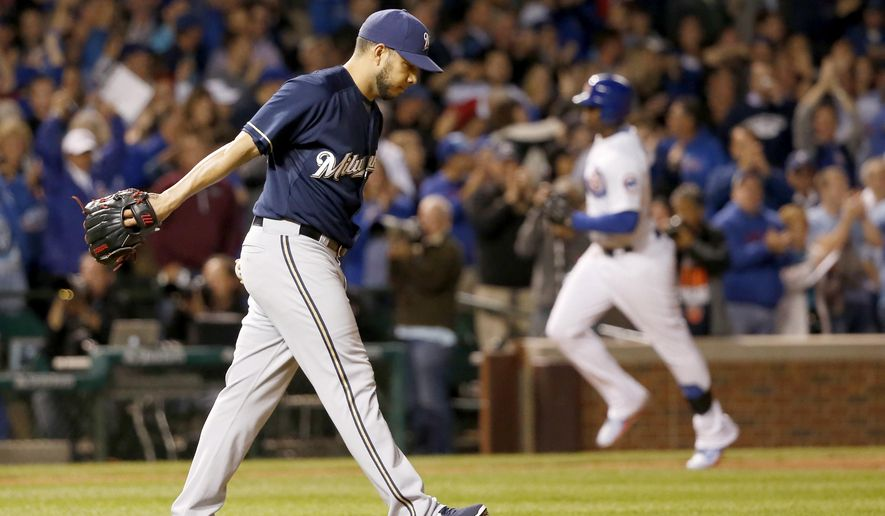 Milwaukee Brewers relief pitcher Cesar Jimenez returns to the mound after giving up a pinch hit, three-run home run to Chicago Cubs' Jorge Soler, right, also scoring Anthony Rizzo and Starlin Castro, during the seventh inning of a baseball game Monday, Sept. 21, 2015, in Chicago. (AP Photo/Charles Rex Arbogast)