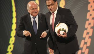 FILE-- In this Friday, Dec. 4, 2009, photo, FIFA President Sepp Blatter, right, hands the official ball for the 2010 soccer World Cup, called Jabulani, to World Cup organising committee CEO Danny Jordaan in Cape Town, South Africa. South Africa's main opposition party, The Democratic Alliance, said it filed papers with police on Monday asking them to investigate the involvement of former World Cup head Danny Jordaan and former South African Football Association President Molefi Oliphant in alleged bribery to get the World Cup. (AP Photo/Denis Farrell, FILE)