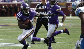 Minnesota Vikings running back Adrian Peterson (28) runs  against the Detroit Lions as Vikings quarterback Teddy Bridgewater (5) watches in the first half of an NFL football game in Minneapolis, Sunday, Sept. 20, 2015. (AP Photo/Ann Heisenfelt)