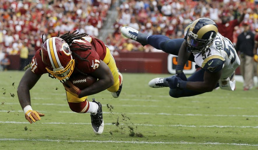 In this photo taken Sept. 20, 2015, Washington Redskins running back Matt Jones (31) dives for extra yardage after breaking a tackle by St. Louis Rams outside linebacker Alec Ogletree (52) during the second half of an NFL football game in Landover, Md. By adding rookie Jones to dependable veteran Alfred Morris, the Washington Redskins have created an unusual two-back rushing attack. How unusual? With Jones running for 123 yards in Week 2, after Morris gained 121 yards in Week 1, the Redskins are the first NFL team since 2006 to have two backs each gain at least 100 yards on the ground in a season's first two games. (AP Photo/Patrick Semansky)