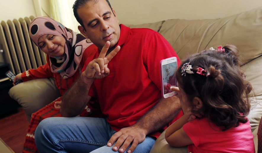 In this Wednesday, Sept. 16, 2015 photo, Hussam Alroustom, center, poses for a cell phone photo by his daughter Maaesa as his wife, Suha, left, looks on in their apartment in Jersey City, N.J. The Alroustom family are Syrian refugees after fleeing their war stricken country. (AP Photo/Julio Cortez)
