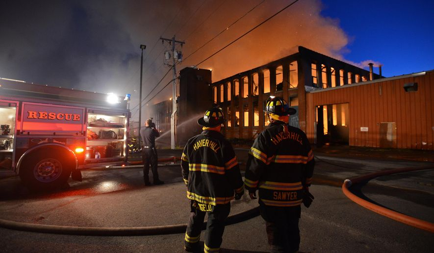 Haverhill firefighters rotate out from fighting the flames still raging at the former Hudson Manufacturing building  in Haverhill, Mass., Sunday, Sept. 20, 2015. The building caught fire around 5 p.m. Sunday. Smoke could be seen 20 miles away by air. Haverhill Fire Chief Jack Parow says the building has been abandoned for a while. (Ryan Hutton/The Eagle-Tribune via AP)