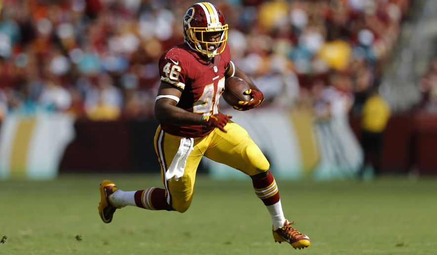 In this photo taken Sept. 13, 2015, Washington Redskins running back Alfred Morris rushes the ball during the second half of an NFL football game against the Miami Dolphins in Landover, Md. By adding rookie Matt Jones to dependable veteran Morris, the Washington Redskins have created an unusual two-back rushing attack. How unusual? With Jones running for 123 yards in Week 2, after Morris gained 121 yards in Week 1, the Redskins are the first NFL team since 2006 to have two backs each gain at least 100 yards on the ground in a season's first two games. (AP Photo/Patrick Semansky)