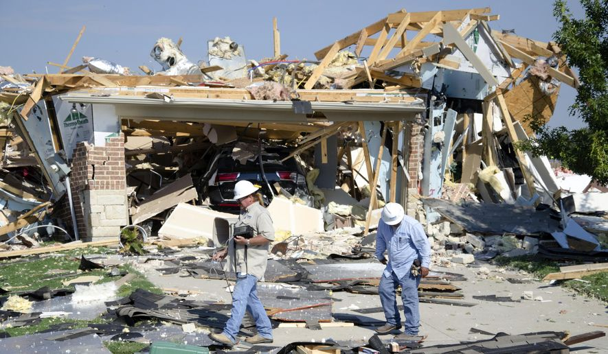 Workers walk around a house that exploded on Monday, Sept. 21, 2015, in Waxahachie, Texas. A couple people were airlifted to a hospital after the explosion. (Scott Dorsett/The Waxahachie Daily Light via AP)