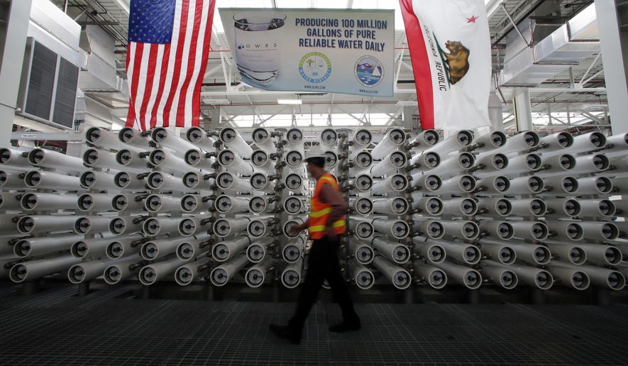 ADVANCE FOR USE SATURDAY, SEPT. 26, 2015 AND THEREAFTER - In this Wednesday, July 29, 2015, photo, Jason Dadakis of the Orange County Water District walks past part of the water filtration system at their water treatment plant in Fountain Valley, Calif. Orange County's myriad efforts to ensure its taps keep flowing can serve as a model for other communities across the nation where water is in short supply. (AP Photo/Chris Carlson)