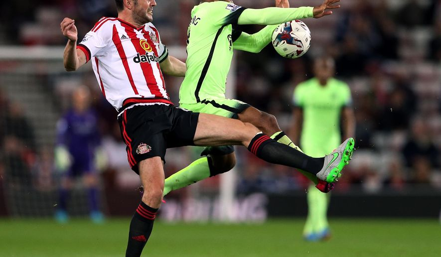 Sunderland's captain John O'Shea, left, vies for the ball with Manchester City's Raheem Sterling, right, during the English League Cup third round soccer match between Sunderland and Manchester City at the Stadium of Light, Sunderland, England, Tuesday, Sept. 22, 2015. (AP Photo/Scott Heppell)