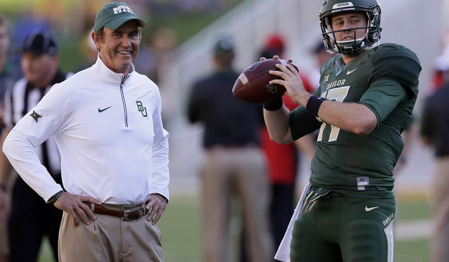 FILE - In this Sept. 12, 2015, file photo, Baylor quarterback Seth Russell (17) warms up as coach Art Briles watches before an NCAA college football game against Lamar in Waco, Texas. Baylor's spread is spreading, and weakening opposing defenses. The top three FBS teams in total offense three weeks into the season are Baylor and two programs (Bowling Green and Tulsa) led by proteges of coach Briles. His player-friendly system is easily transferrable and highly effective.  (AP Photo/LM Otero, File)