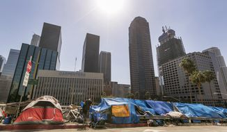 Tents used by the homeless line a downtown Los Angeles street with the skyline behind Tuesday, Sept. 22, 2015. Los Angeles officials say they will declare a state of emergency on homelessness and propose spending $100 million to reduce the number of people living on city streets. City Council President Herb Wesson, members of the council's Homelessness and Poverty Committee and Mayor Eric Garcetti announced the plan Tuesday outside City Hall, as homeless people dozed nearby on a lawn.(AP Photo/Damian Dovarganes)