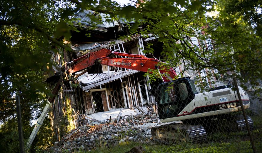 A demolition crew works to tear down a 150-year-old seminary located on 300 block of West High Street on Tuesday, Sept. 22, 2015, in Fenton, Mich. The Seminary, built in 1867, has been vacant since 1967 and a failing foundation was the reason for demolition. (Danny Miller/The Flint Journal-MLive.com via AP)