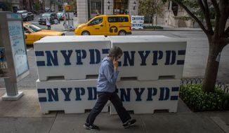 A pedestrian passes NYPD concrete barriers near the residence to the Vatican's ambassador to the United Nations, where Pope Francis is scheduled to stay, Tuesday, Sept. 22, 2015, in New York. (AP Photo/Bryan R. Smith)