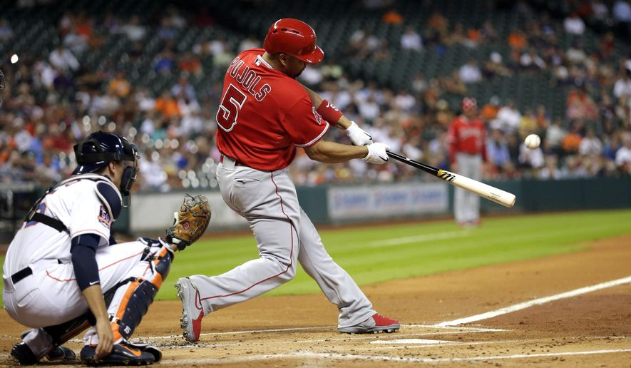 Los Angeles Angels' Albert Pujols hits a home run next to Houston Astros catcher Jason Castro during the first inning of a baseball game Tuesday, Sept. 22, 2015, in Houston. (AP Photo/David J. Phillip)