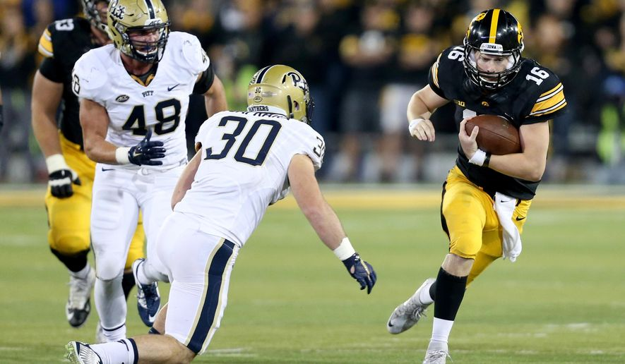 Iowa quarterback C.J. Beathard scrambles away from Pittsburgh defensive lineman Zach Poker and linebacker Mike Caprara on the final drive of the NCAA college football game, Saturday, Sept. 19, 2015, in Iowa City, Iowa. (AP Photo/Justin Hayworth)