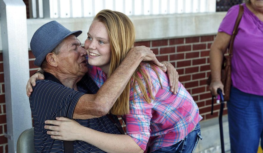 "In this Monday, Sept. 21, 2015 photo, Ashley Aldridge, of Auburn, Ill., hugs Earl Moorman, 75, in Chatham, Ill., whom she freed from his motorized wheelchair after it became stuck at a railroad crossing seconds before a train crashed into it last week in Auburn. Aldridge was honored as a ""Hometown Hero"" and given a supermarket shopping spree in Chatham. (Ted Schurter/The State Journal-Register via AP) MANDATORY CREDIT, NO SALES"
