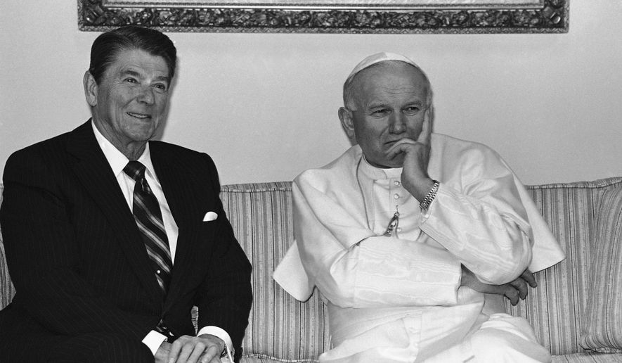 FILE - In this May 2, 1984 file photo, Pope John Paul II strike a pensive pose as he and President Ronald Reagan sit for photographers prior to having a private meeting in Fairbanks, Alaska at the airport.    After the meeting Reagan left for Washington and the pope for South Korea. (AP Photo/Scott Stewart)