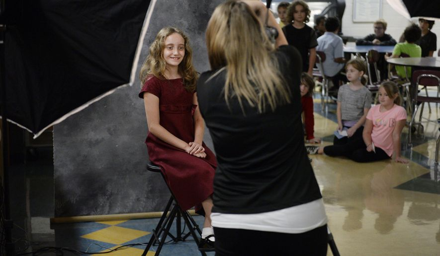 Sophia Hatcher, a fifth grader, smiles for Pettit and Associates photographer Chelsae Hooper during picture day at Templeton Elementary School in Bloomington, Ind. Tuesday, Sept. 15, 2015. (Chris Howell/The Herald-Times via AP) MANDATORY CREDIT