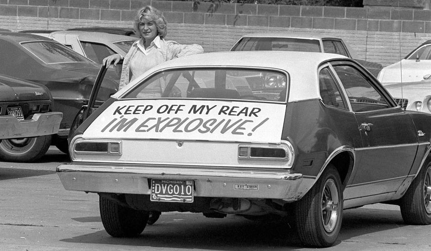 FILE - In this Sept. 1, 1978 file photo, Patty Ramge poses with her 1975 Ford Pinto that bears a sign warning fellow motorists to keep their distance, in Detroit. Ramge posted the warning after weeks of trying to convince Ford Motor Co., and its dealers to modify the Pinto's fuel tank so it would not pose a fire hazard in a rear-end crash. At least 27 people died during the 1970s due to the faulty position of fuel tanks in the Ford Pinto. (AP Photo/JCH, File)