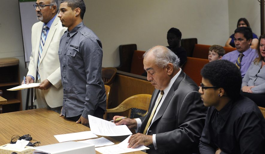 Andre Thompson, left, and Bryson Chaplin, right, appear before Superior Court Judge Gary Tabor during their arraignment in connection with a May 2015 shoplifting incident and their subsequent shooting by Olympia Police officer Ryan Donald, Tuesday, Sept. 22. 2015 in Olympia,Wash.. Both entered not guilty pleas and were represented by attorneys George Trejo, second from right, and Daryl Rodrigues, far left, director of the Office of Assigned Counsel. (Steve Bloom/The Olympian via AP)
