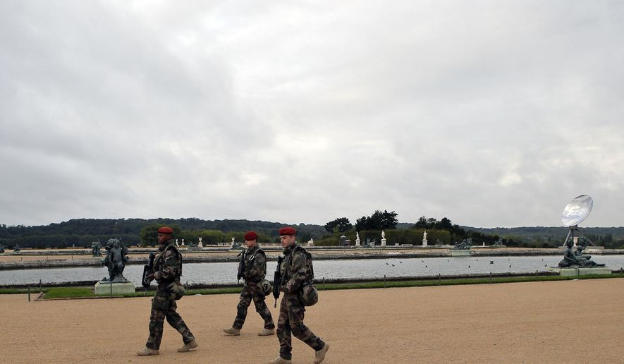 """French army soldiers patrol early morning next to the vandalized sculpture """"Dirty Corner"""" by British-Indian artist Anish Kapoor in the Versailles castle, Tuesday, Sept. 22, 2015 in Versailles, outside Paris, France. The controversial red trumpet-shaped work by the British-Indian Jewish sculptor was dubbed the """"Queen's Vagina"""" by media and has been vandalized three times since its installation in June in the conservative town of Versailles. (AP Photo/Francois Mori)"""