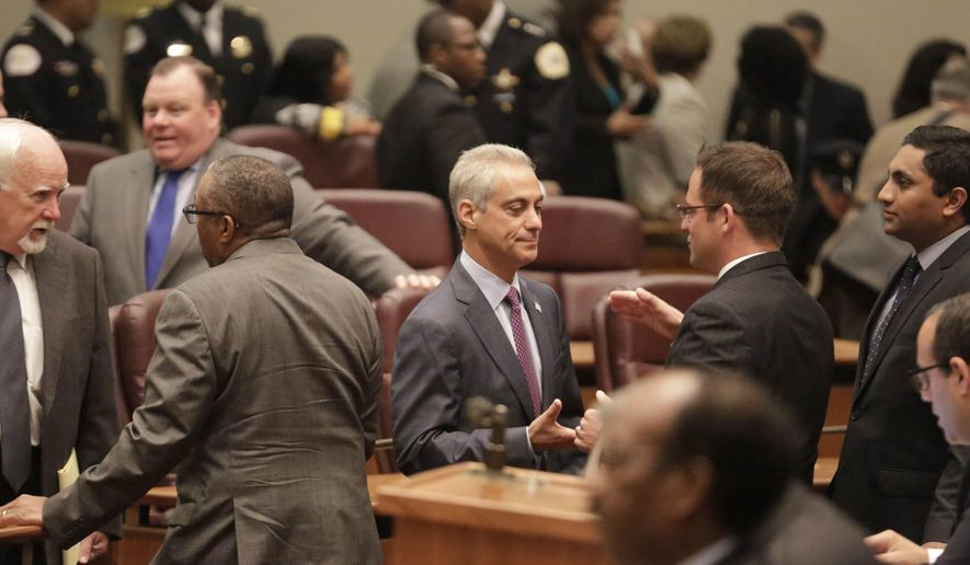 Mayor Rahm Emanuel, center, shakes hands in Council chambers before outlining his 2016 proposed budget to the City Council Tuesday, Sept. 22, 2015, in Chicago. In his speech Emanuel called for a phased-in $543 million property tax increase, along with $45 million more for schools. He also called for other fees, including for garbage collection and ride-sharing services. (AP Photo/M. Spencer Green)