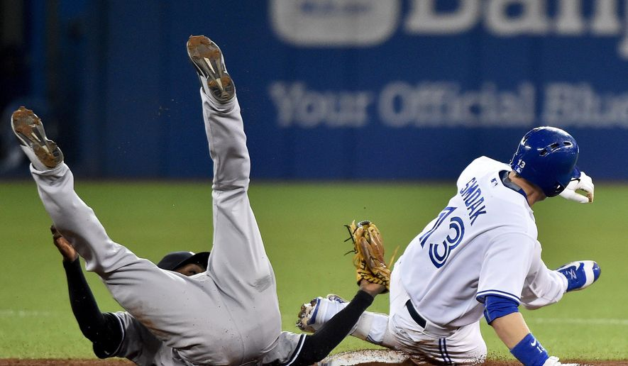 Toronto Blue Jays' Justin Smoak, right, is tagged out at second base by New York Yankees' shortstop Didi Gregorius during the fourth inning of a baseball game Tuesday, Sept. 22, 2015, in Toronto. (Nathan Denette/The Canadian Press via AP) MANDATORY CREDIT
