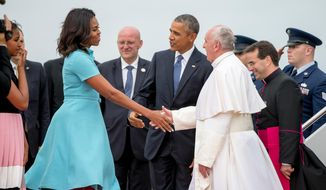 First lady Michelle Obama, accompanied by President Obama, greets Pope Francis upon his arrival at Andrews Air Force Base on Tuesday. (AP Photo)
