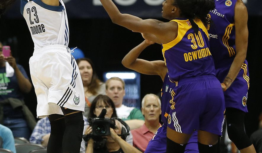 Minnesota Lynx forward Maya Moore (23) shoots the ball against the defense of Los Angeles Sparks forward Nneka Ogwumike (30) and center Candace Parker (3) during the first half of Game 3 of a WNBA basketball Western Conference semifinal series, Tuesday, Sept. 22, 2015, in Minneapolis. (AP Photo/Stacy Bengs)