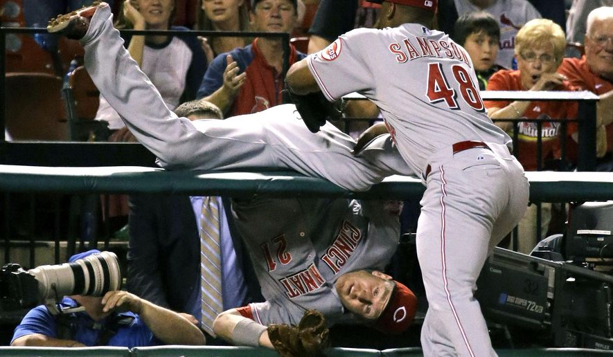 Cincinnati Reds third baseman Todd Frazier, left, is held back from falling further into a photo pit by teammate Keyvius Sampson after catching a foul ball hit by St. Louis Cardinals' Matt Adams for an out during the fourth inning of a baseball game on Tuesday, Sept. 22, 2015, in St. Louis. (AP Photo/Jeff Roberson)