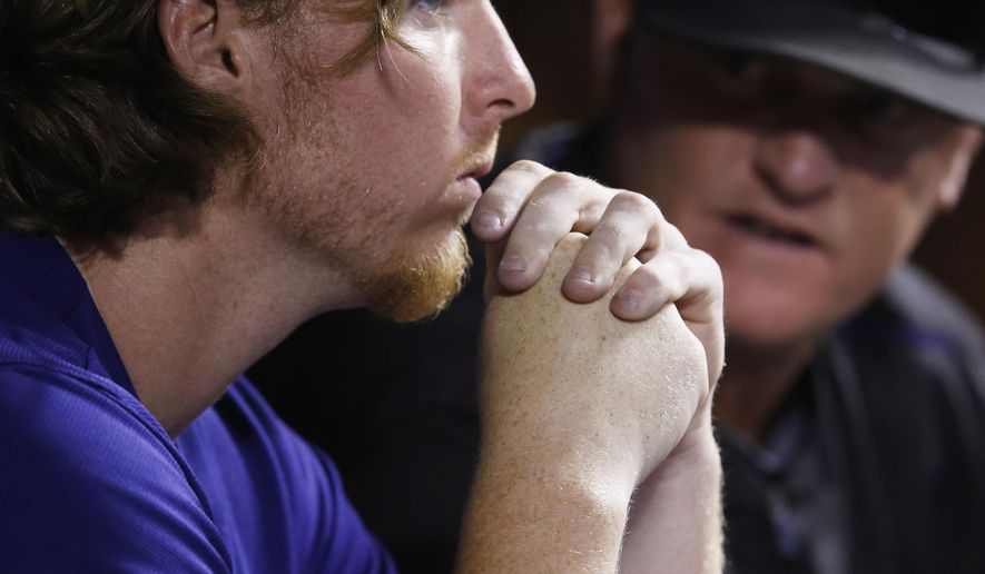 Colorado Rockies starting pitcher Jon Gray, front, confers with pitching coach Steve Foster after Gray was pulled from the mound against the Pittsburgh Pirates in the fifth inning of a baseball game Monday, Sept. 21, 2015, in Denver. (AP Photo/David Zalubowski)