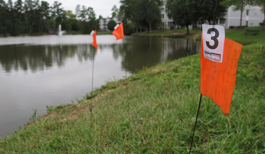 Orange evidence flags line the shore of a pond in the Audubon Lake neighborhood of Durham, N.C. on Tuesday, Sept. 22, 2015. Police say Alan Tysheen Eugene Lassiter attempted to drown his three young children, two of whom remain hospitalized. (AP Photo/Allen G. Breed)