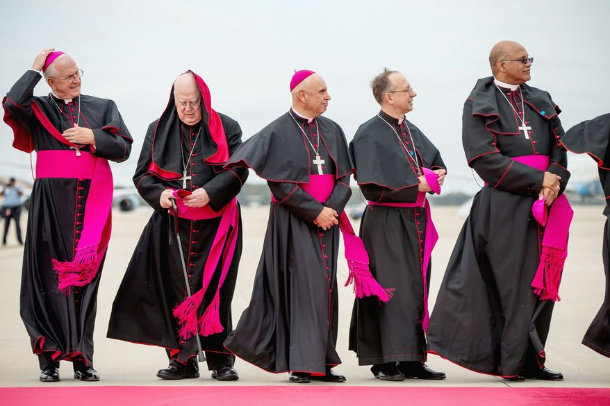 Clergy brace for the wind as they stand along the red carpet on the tarmac at Andrews Air Force Base, Md., Tuesday, Sept. 22, 2015, as the plane carrying Pope Francis arrives. (AP Photo/Andrew Harnik)